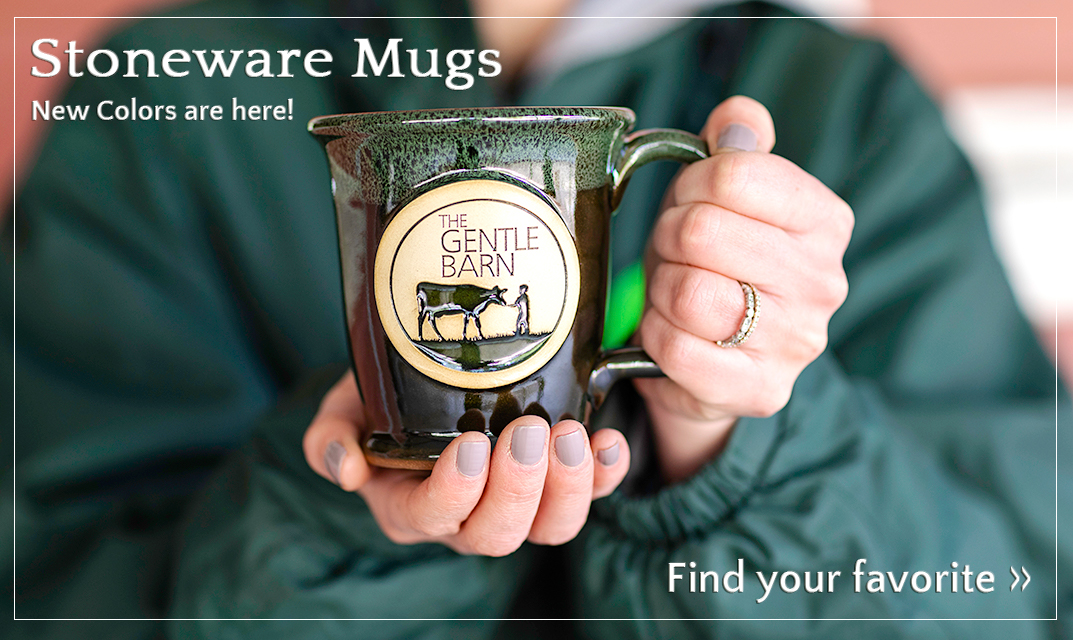 A woman is holding one of our Gentle Barn stoneware mugs with our logo. Click to shop all Gentle Barn Home Goods.