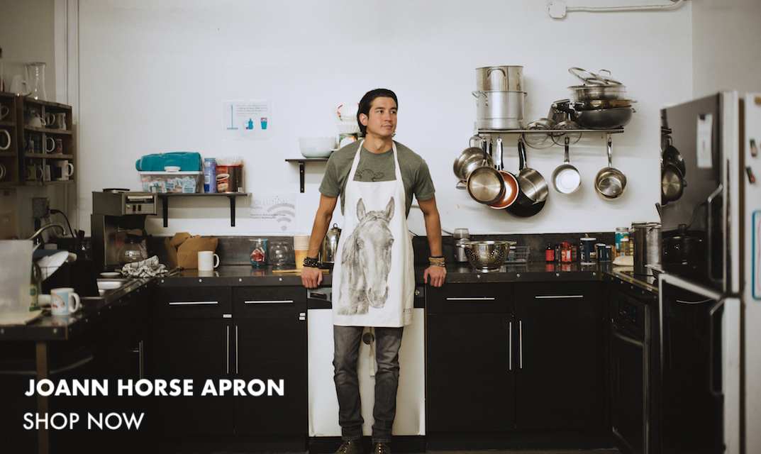 This is an image of a man standing in a kitchen wearing an apron featuring Joann the horse. Click to buy this apron!