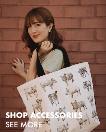 This is an image of a woman carrying a large canvas tote bag with drawings of pigs on it. Click to shop our accessories.